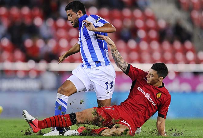 Carlos Vela of Real Sociedad duels for the ball with Joaquin Navarro of RCD Mallorca in a La Liga match.