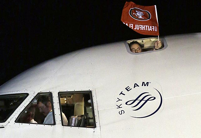 Captain Bruce Eaton waves a flag as the San Francisco 49ers arrive at the Louis Armstrong International Airport.