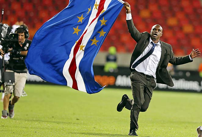 Coach Lucio Antunes runs with Cape Verde's flag after winning at the Africa Cup of Nations.