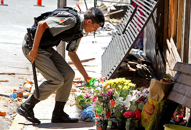 A police officer places flowers outside the Kiss nightclub that were brought by mourners.