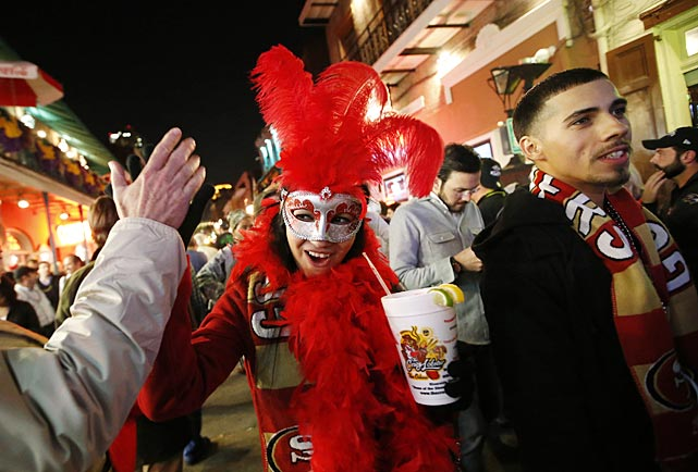 Blanca Espericueta, of San Francisco, high-fives a man as she walks along Bourbon Street in the French Quarter