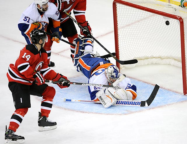 New Jersey Devils center Adam Henrique lifts the puck into the top-right corner of the goal, past New York Islanders goaltender Evgeni Nabokov in the third period. Henrique's goal tied the game at four, but the Islanders earned the victory on an overtime goal from right winger Brad Boyes.
