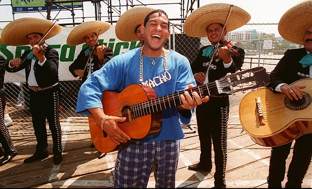 "The boxer plays guitar with the ""Mariachi Regional Ranchero"" at the Santa Monica, CA, pier on July 7, 1997."
