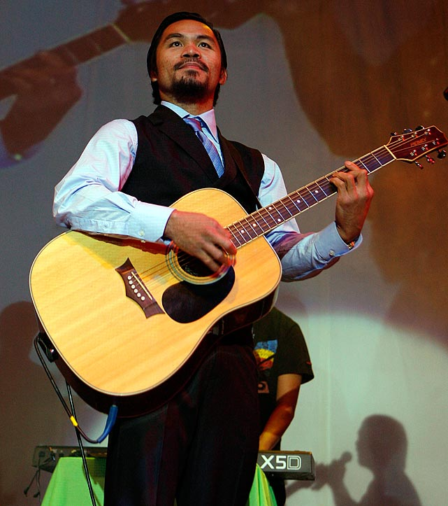 The boxer and Philippine Congressman-elect plays guitar during his victory party in General Santos City, southern Philippines on May 15, 2010.