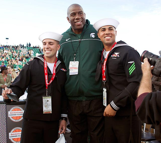 Sailors Christopher Huff, left, and Andrew Morgan pose with NBA great and Michigan State alum Magic Johnson aboard the USS Carl Vinson in San Diego in 2011.
