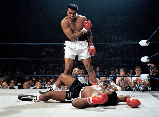 "In one of the most iconic and controversial moments of his career, Ali stands over Sonny Liston and yells at him after knocking the former champ down in the first round of their 1965 rematch. Skeptics dubbed it ""the Phantom Punch,"" but films show that Ali's flashing right caught Liston flush, knocking him to the canvas. Refusing to go to a neutral corner, Ali stood over Liston and told him to ""get up and fight, sucker."" Click here for Neil Leifer's fine art photography."