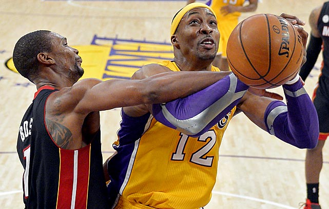 Miami's Chris Bosh does his best to keep Lakers center Dwight Howard from muscling up a shot.