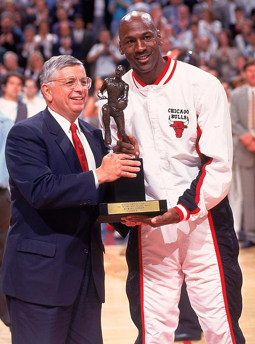Michael Jordan receives the Maurice Podoloff Trophy from NBA commissioner David Stern before Game 2 of the 1996 Eastern Conference Finals. In his first full season back from his first retirement, Jordan won his fourth MVP Award, leading the league with 30.4 points per game.