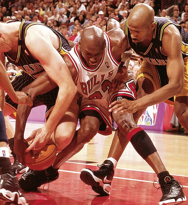 Jordan fights for a loose ball with Rik Smits and Derrick McKey of the Indiana Pacers in Game 7 of the 1998 Eastern Conference Finals. In a tremendous all-around performance, Jordan led the Bulls with 28 points, nine rebounds and eight assists to return to the NBA Finals.