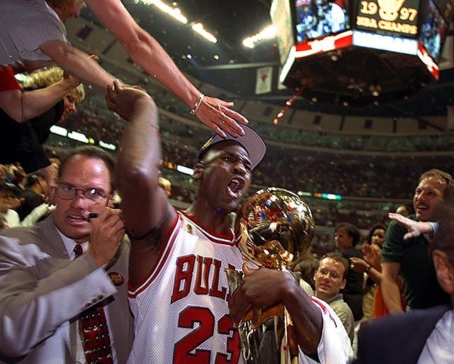 Jordan clasps the Larry O'Brien Trophy and high-fives some fans after winning the 1997 NBA Finals, the fifth championship of his career. The Bulls downed the Utah Jazz in six games, and Jordan was named Finals MVP, avenging his loss to the Jazz's Karl Malone for the regular season MVP.