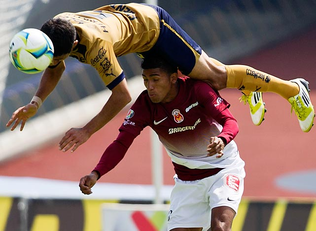 Pumas' Luis Fuentes leaps over Morelia's Aldo Leao to head the ball in a Mexican soccer league match in Mexico City on Feb. 17. Efrain Velarde scored the lone goal of the game for Pumas in the 65th minute.