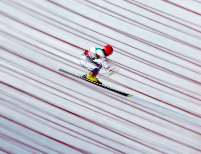 In a long time exposed photo taken through a safety fence, a skier races during the first run of the men's giant slalom at the alpine skiing world championships in Schladming, Austria. Ted Ligety won the event, becoming the first to win three individual gold medals at the world championships since Jean-Claude Killy in 1968.