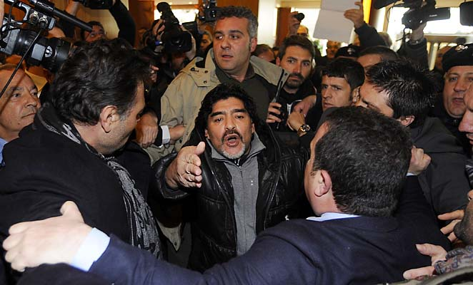 Diego Maradona makes his way through journalists as he arrives in Naples, Italy, on Monday.