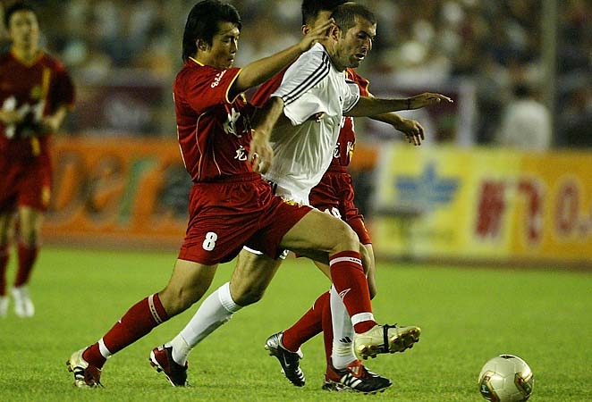 Shen Si (left) fights for the ball with Zinedine Zidane in a 2003 match.