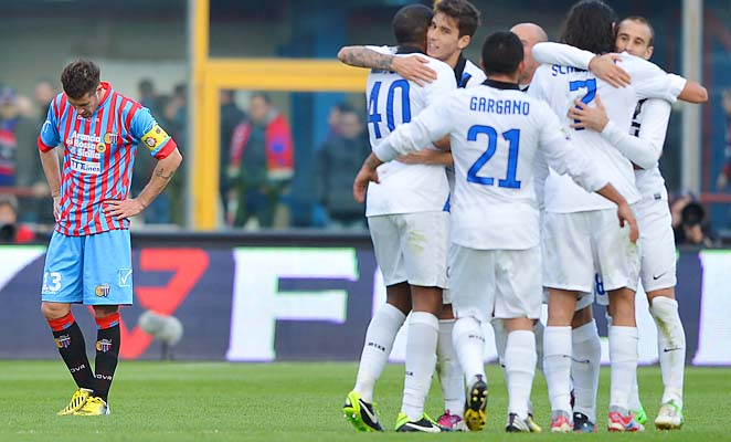 Catania midfielder Mariano Izco (left) reacts as Inter Milan players celebrate their victory.