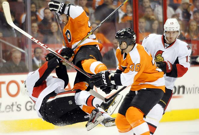 The Flyers' Harry Zolnierczyk (left) hits the Senators' Mike Lundin in Saturday's game.