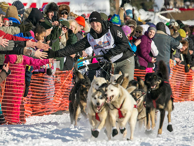 Dallas Seavey, winner of the 2012 Iditarod, high fives fans on his way out onto the trail.