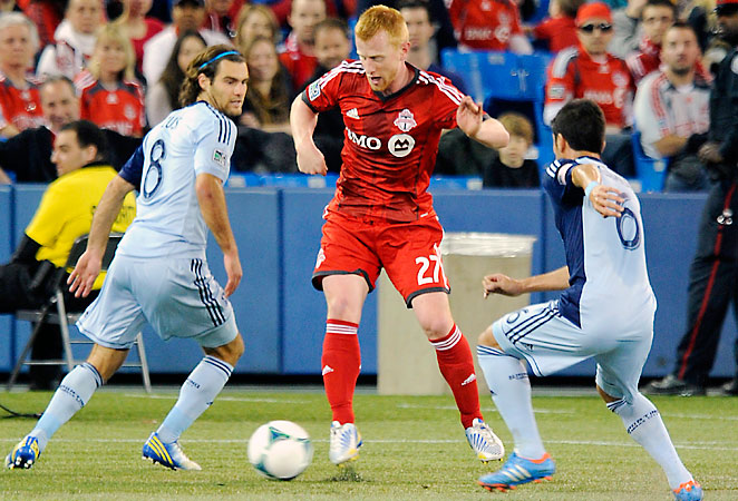 Toronto FC defender Richard Eckersley dribbles past Sporting Kansas City's Graham Zusi and Paulo Nagamura in Saturday afternoon's game.