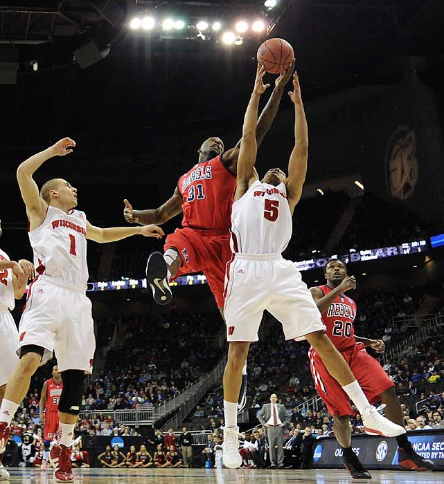 Ole Miss forward Murphy Holloway gets air to snatch the ball from the outreached hands of the Badgers' Ryan Evans.