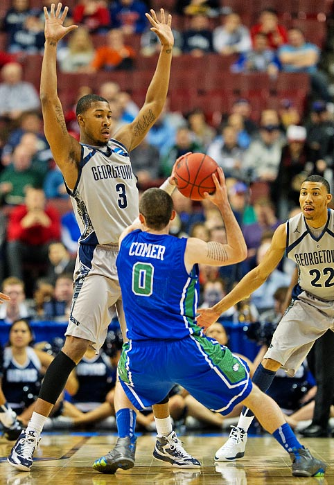 Florida Gulf Coast's Brett Comer battles Georgetown's Michael Hopkins on an offensive possession.