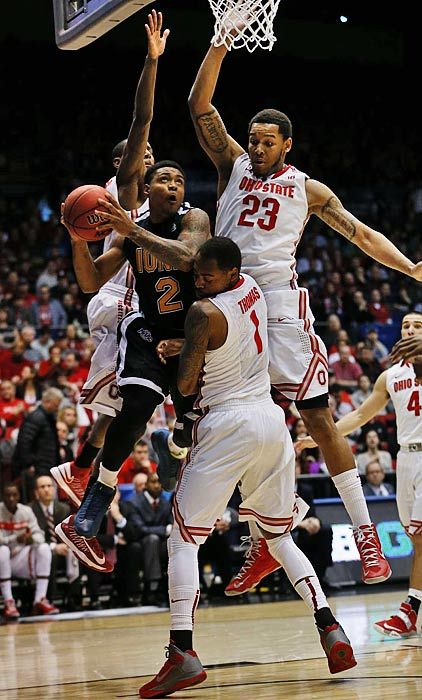 Iona's Lamont Jones is surrounded by Ohio State defenders as he goes in for a layup.