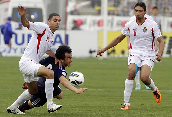 Japan's Uchida Atsuto vies for the ball against Jordan's Basem Fathi (left) and Mohammed Saeed (right).