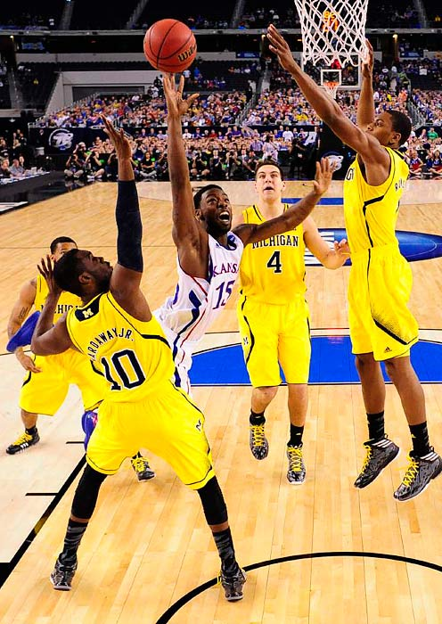 <bold>Kansas guard Elijah Johnson drives into the paint for a layup against Michigan. Johnson missed a free throw and threw a pass on a potentially game-tying drive in the dying seconds of the Michigan win. </bold> <bold>Defeated S. Dakota State 71-56</bold> <bold>Defeated VCU 78-53</bold> <bold>Defeated Kansas 87-85</bold>