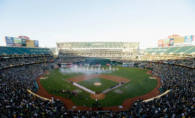 The Oakland Athletics and the Seattle Mariners stand for the singing of the National Anthem during Opening Day at O.co Coliseum.