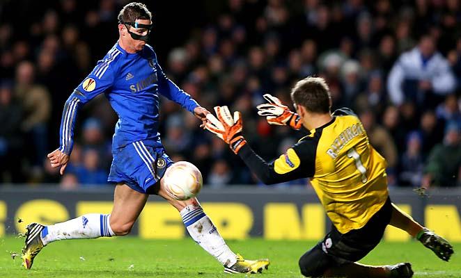 Masked Fernando Torres closes in on Rubin Kazan goalie Sergei Ryzhikov.