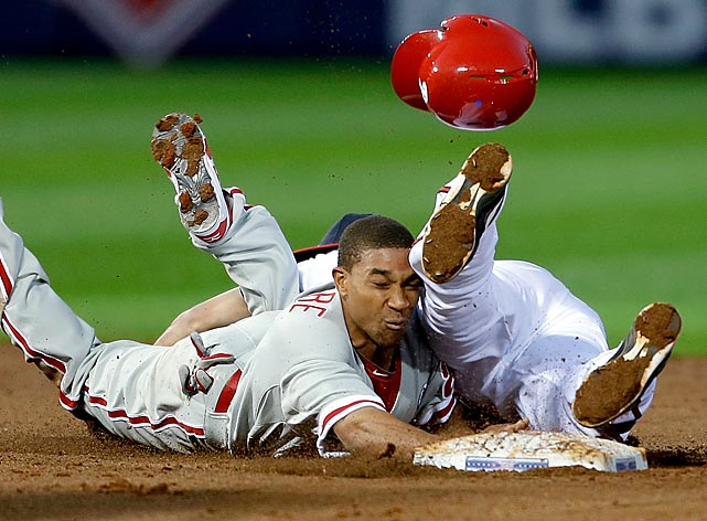 The Phillies' Ben Revere loses his helmet while colliding with the Braves' Andrelton Simmons on a dive back to second base.