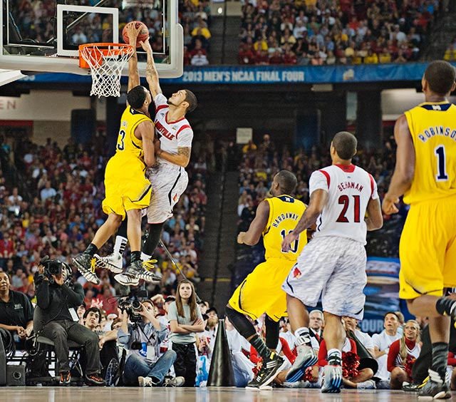Michigan's Trey Burke was called for a foul while blocking this Peyton Siva shot late in the second half.