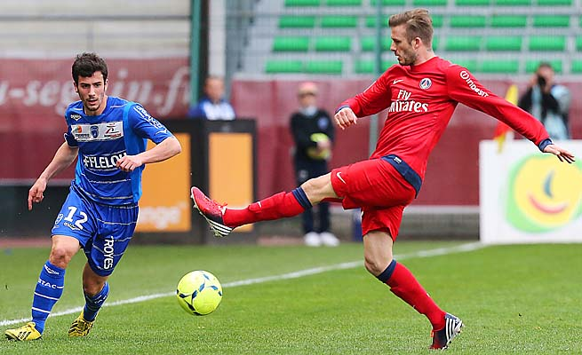Troyes defender Maxime Colin (left) vies for the ball with PSG midfielder David Beckham.