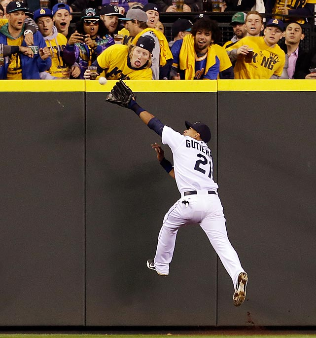 Seattle Mariners left fielder Franklin Gutierrez leaps at the ball against the Texas Rangers in the seventh inning of the Mariners' 4-3 loss.