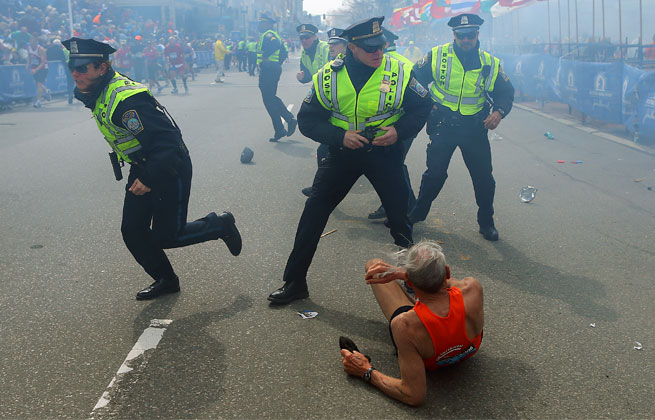 Police officers hear the second explosion down the street. The first explosion knocked down a runner at the finish line.