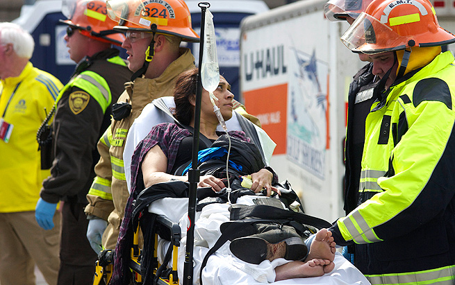 A woman is carried away on a stretcher after two bombs exploded at the finish of the Boston Marathon.