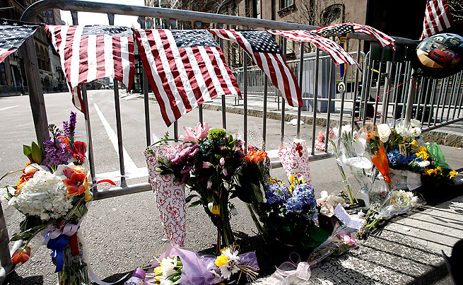 Flowers sit at a police barrier near the finish line to honor the victims of the Boston Marathon bombing.