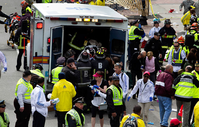 First responders load injured people into an ambulance where two explosions occurred along the final stretch of the Boston Marathon.