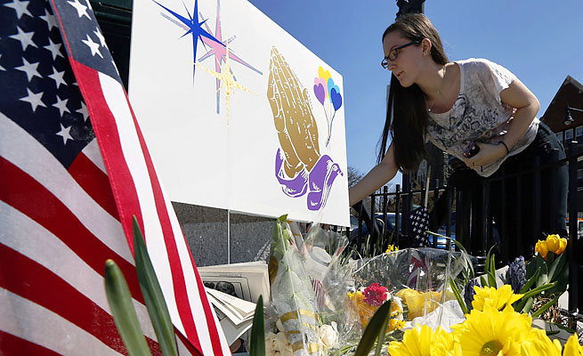 Shannon Walsh, 15, puts flowers on a memorial to Boston Marathon bombing victim Martin Richard, 8.