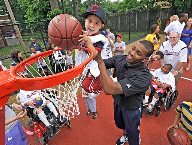 Cavaliers forward Alonzo Gee helps a young boy get closer to the rim at the newly remodeled basketball courts at the Cleveland Clinic Children's Hospital for Rehabilitation.