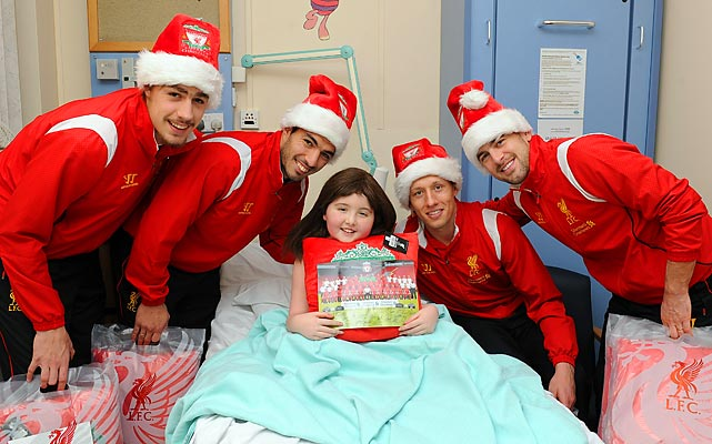 Liverpool players Sebastian Coates, Luis Suarez, Lucas Leiva and Joe Cole (who now plays for West Ham) visit a girl in Alder Hey Children's Hospital in England.