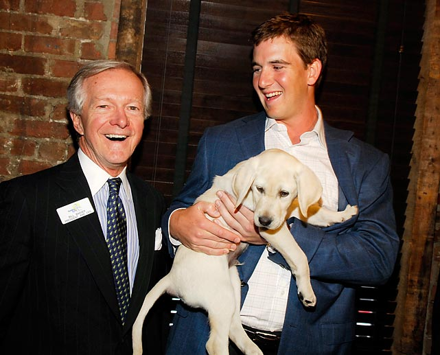 Giants quarterback Eli Manning carries his namesake, guide dog trainee Eli, into the Guiding Eyes for the Blind's Spring Tee Off in New York alongside Guiding Eyes president and CEO Bill Badger.
