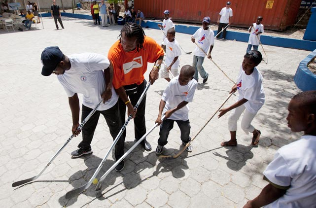 Former NHL player Georges Laraque (right) and Montreal Canadiens player P.K. Subban (left) play street hockey with patients at Grace Children's Hospital in Haiti.