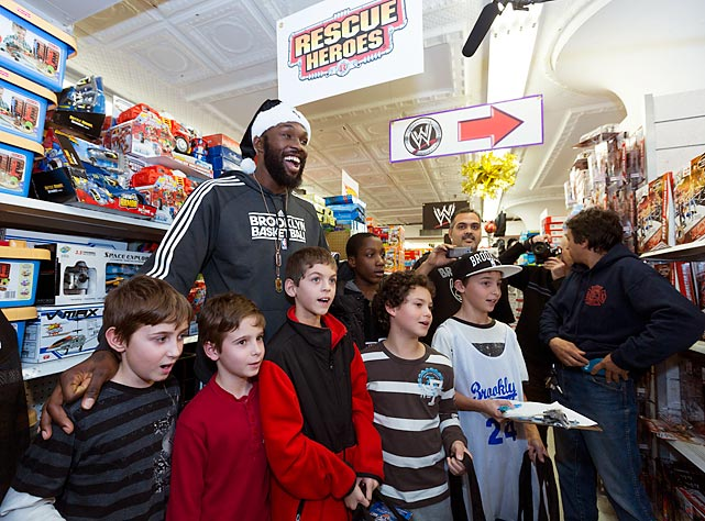 Nets forward Reggie Evans takes kids displaced by Hurricane Sandy shopping at Cookies Department Store in New York.