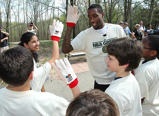 Grizzlies guard Tony Wroten high-fives kids while cleaning up during the NBA's Green Week at the Wolf River Greenway in Memphis.