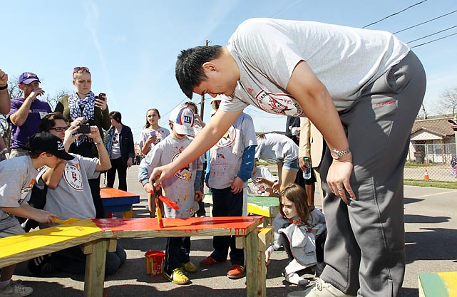 Yao Ming paints benches with children as part of the 2013 NBA Cares Day of Service at the KaBOOM! Playground Build in Houston.