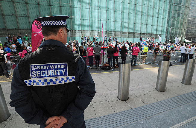 A Canary Wharf Security guard keeps an eye on the crowd and race during the Virgin London Marathon.