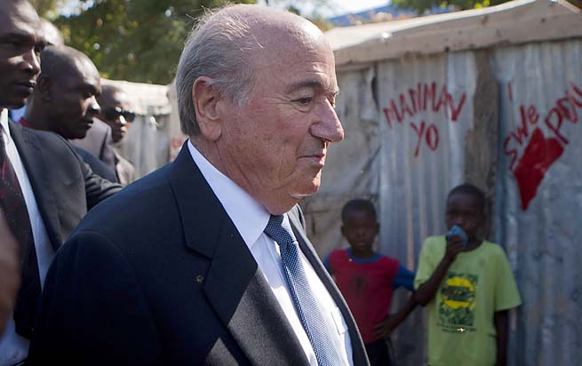 Sepp Blatter walks through a refugee camp in Haiti last week.