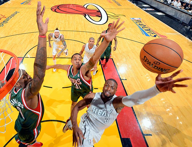 Larry Sanders (8) of the Milwaukee Bucks tries to get a hand on Dwyane Wade's layup in Game 1 on their series against the Heat Sunday. Miami coasted to a 110-87 victory.