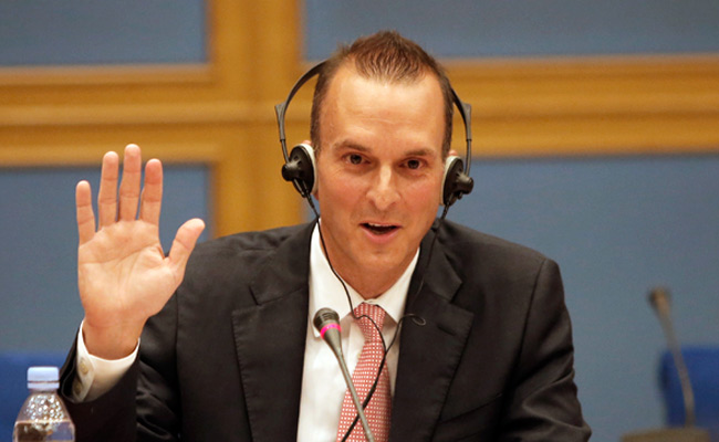 Travis Tygart, the head of the USADA, takes an oath during a French government Senate hearing.