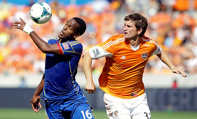 Rapids striker Atiba Harris, left, controls the ball while guarded by Dynamo defender Bobby Boswell.
